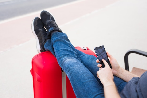 Travel, tourism and people concept. handsome man sits and put his feet on suitcase, watching something in his mobile.