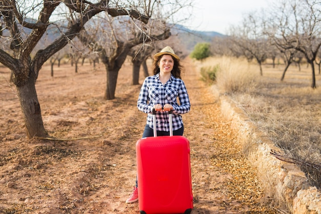 Travel, tourism and people concept - happy young woman going to travel by with red suitcase and