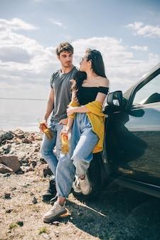 旅行、観光-水の近くのピクニック。冒険に行くカップル。車の旅のコンセプト。男と女はビールを飲みます。