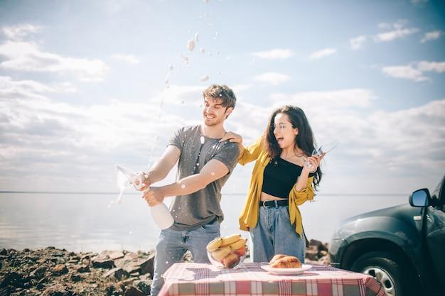 旅行、観光-水の近くのピクニック。冒険に行くカップル。車の旅のコンセプト。男性と女性はシャンパンを飲みます。