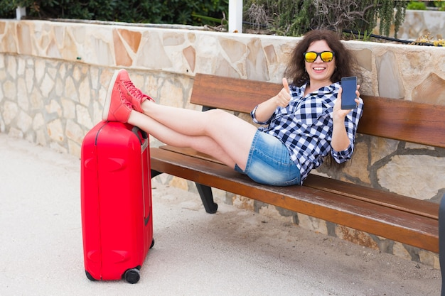 여행, 관광, 기술 및 사람 개념입니다. 행복한 젊은 여성은 벤치에 앉아 가방에 발을 올려놓고 휴대전화를 보여줍니다.