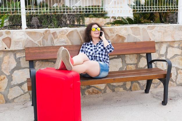 여행, 관광, 기술 및 사람 개념입니다. 행복 한 젊은 여자는 벤치에 앉아서 가방에 그녀의 발을 넣어