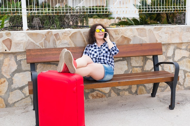 Travel, tourism, technology and people concept. happy young woman sit on bench and put her feet on suitcase