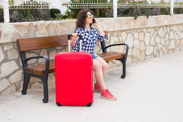 Travel, tourism, technology and people concept. young woman in sunny glasses sit on the bench with red suitcase and talk on the mobile.