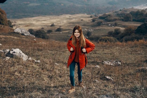 秋の山の中で赤いジャケットとジーンズのバックパックを持った旅行観光の若い女性