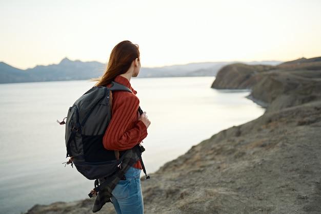 山の自然の中で海沿いのバックパックと旅行観光の若い女性