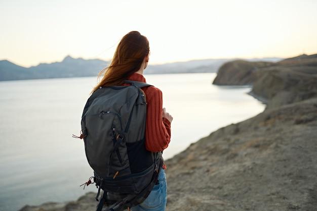 山の自然の海でバックパックを持つ旅行観光若い女性
