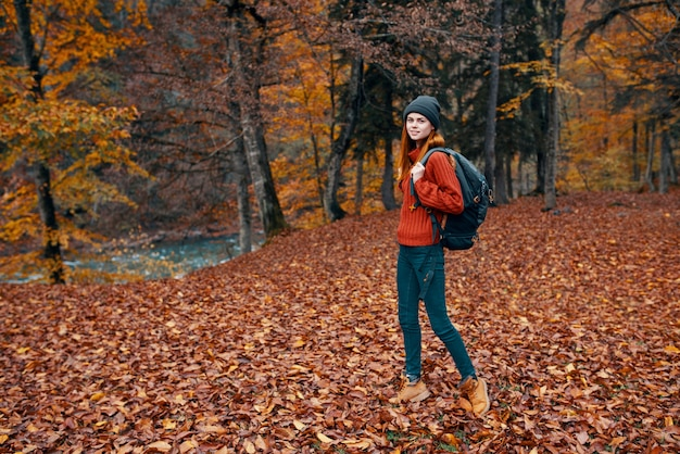 Travel tourism and a young woman with a backpack walks in the park in nature landscape tall trees