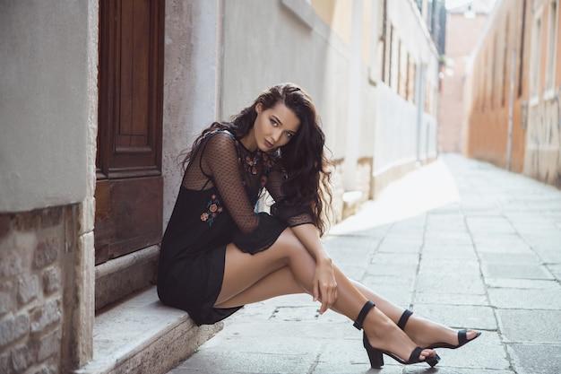 ハイヒールの靴で美しい脚を持つ街の通りでポーズをとって休暇で旅行観光の女の子