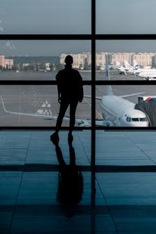공항 창에 서있는 관광 여행. 출발 전에 탑승 게이트에서 기다리는 동안 비행기를보고 라운지를보고 인식 할 수없는 여자.