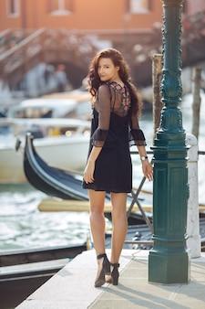 イタリア、ヴェネツィアのヴェネツィアのチャナルの美しい景色を背景に桟橋で観光客の女性を旅行します。
