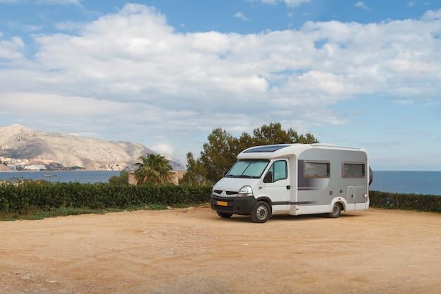 Туристический автофургон с прицепом припаркован в красивом кемпинге с видом на море и горы.