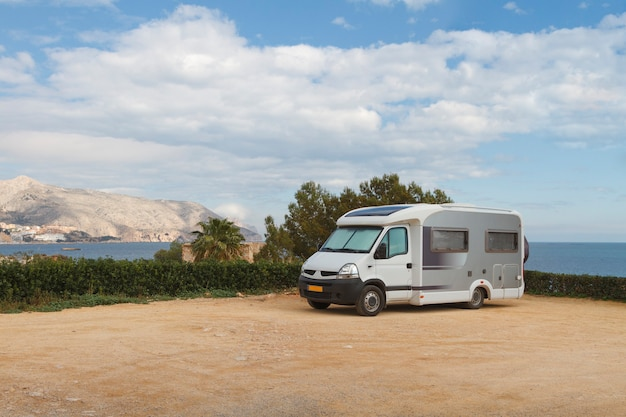 Travel trailer camper van parked at a beautiful camping with seaside and mountains landscape views.