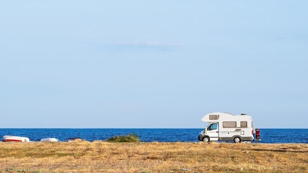 ギリシャ、アスプロバルタの背景と青い空に海と旅行トレーラー