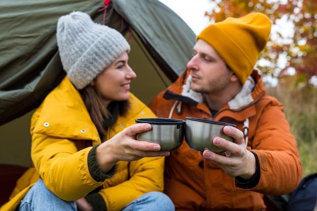 旅行、トレッキング、ハイキングのコンセプト-秋の森の緑のテントの近くでお茶やコーヒーを飲むカップルの肖像画