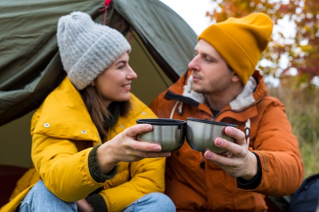 Travel, trekking and hiking concept - portrait of couple drinking tea or coffee near green tent in autumn forest