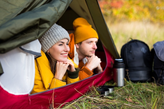 Travel, trekking and hiking concept - portrait of happy couple lying in tent in autumn forest