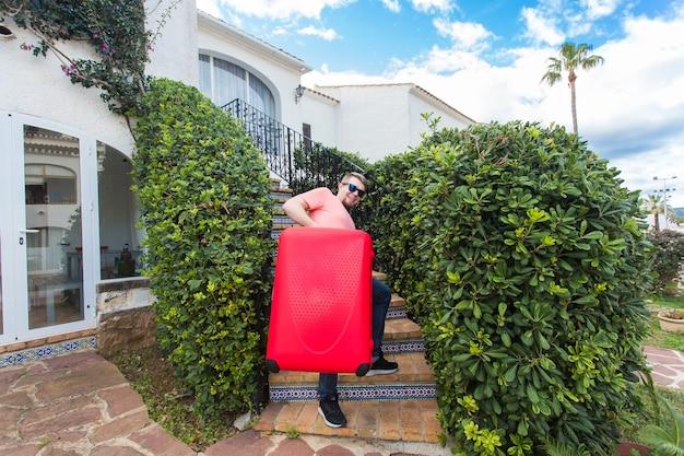 여행, 여행 및 휴일 개념입니다. 계단에 서 있는 맑은 안경에 빨간 가방을 가진 젊은 남자.