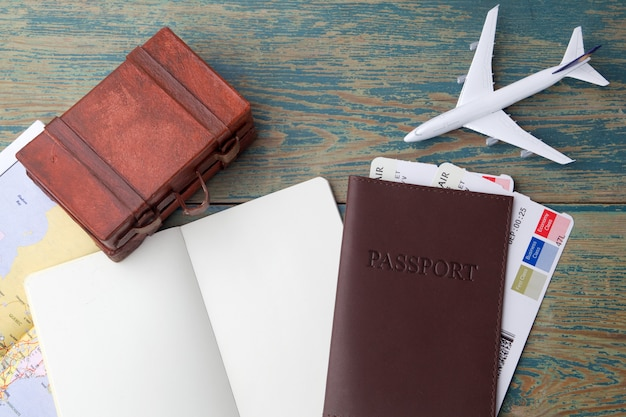 Путешествие, отпуск поездки, туризм - крупным планом записная книжка, чемодан, игрушечный самолетик и туристическая карта на деревянном столе.
