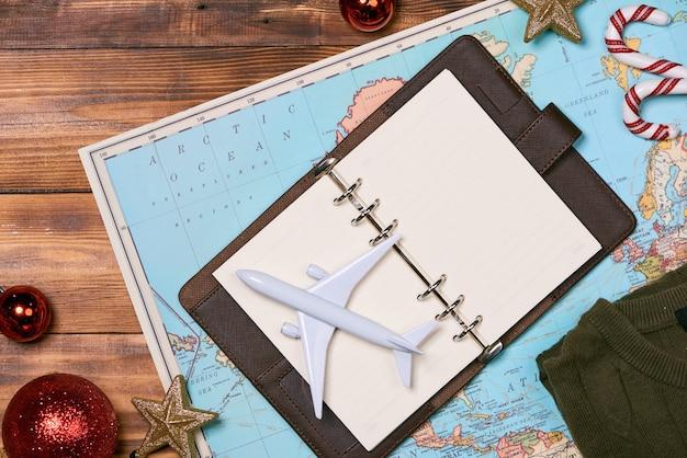 Путешествие, отпуск поездки, макет туризма - крупный план одежды, рождественских украшений и игрушечного самолета и туристической карты на деревянном столе. на пустом месте вы можете разместить свой текст или информацию.