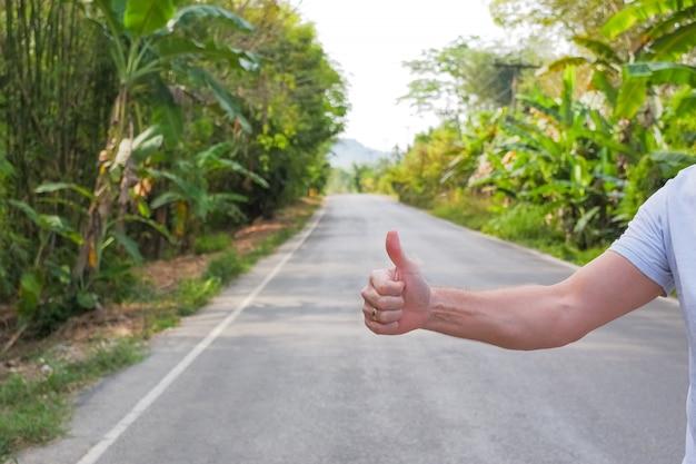 旅行、旅行、休暇、放浪癖。ヒッチハイカーサインオン道路