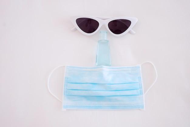 Covid-19と新しい通常のコンセプトの下での旅行医療用フェイスマスク、ハンドゲル消毒剤、サングラス、白いベッドの上で、コロナウイルスやコロナウイルス病を予防