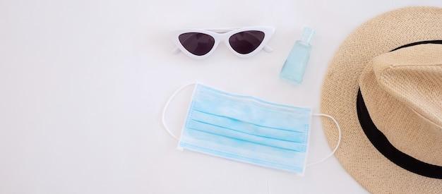 Covid-19と新しい通常のコンセプトの下での旅行医療用フェイスマスク、ハンドジェルサニタイザー、サングラス、白いベッドのビーチハットは、コロナウイルスやコロナウイルス病を防ぎます