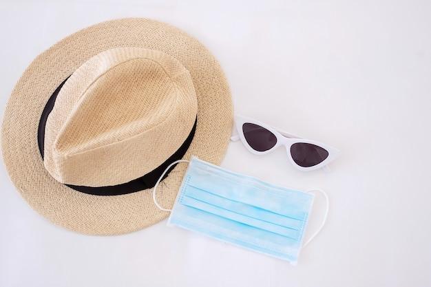Путешествуйте в условиях covid-19 и новых нормальных концепций. медицинская маска для лица, солнцезащитные очки и пляжная шляпа на белой кровати, предотвращение коронавируса или коронавируса