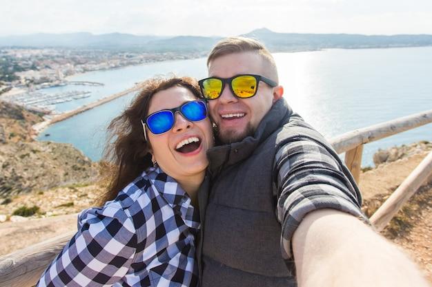 여행, 휴가 및 휴가 개념-아름 다운 커플 재미, selfie, 미친 감정적 인 얼굴을 복용 하 고 웃 고.