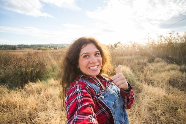旅行、休暇、休日のコンセプト-美しい風景の上に自分撮りを取っている面白い若い女性。