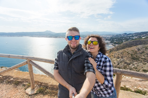 旅行、休暇、休日のコンセプト-美しい風景を自分撮りする幸せなカップル