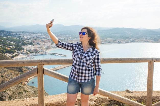 여행, 휴가 및 휴가 개념-재미, 셀카, 미친 감정적 인 얼굴을 복용하고 웃고 젊은 여자.