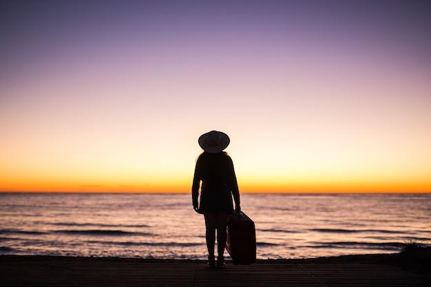 旅行、休暇、休日のコンセプト-夕暮れ時の海の砂浜にスーツケースを持って立っている若い女性。