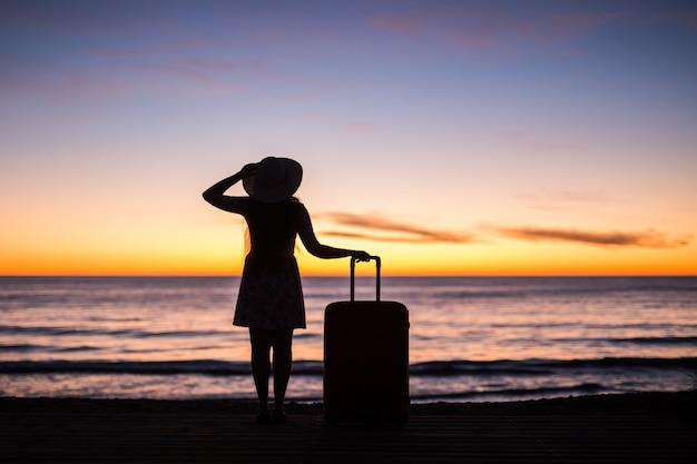 で海の砂浜にスーツケースを持って立っている旅行休暇と休日の概念の若い女性