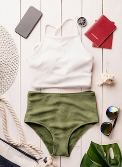 Travel and vacation concept. flat lay travelling objects with swimsuit, smartphone, passports, sunglasses and compass on white wooden background