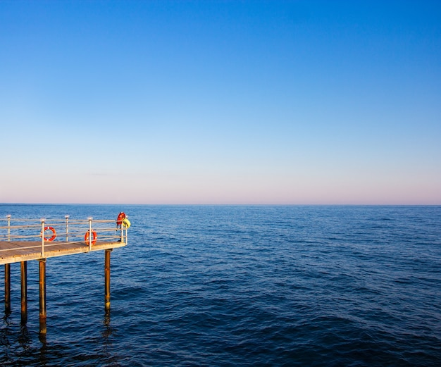 Travel and vacation concept - wooden pier in blue sea