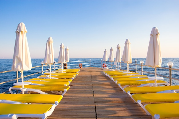 Travel and vacation concept - wooden pier with chairs and umbrellas in blue sea