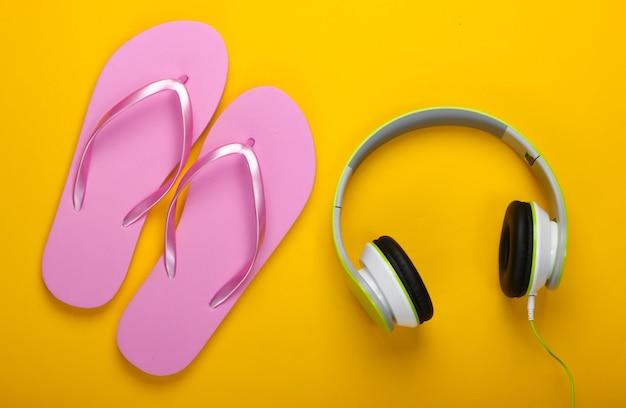 旅行、ビーチでの休暇のコンセプト。黄色い表面にビーチサンダルとヘッドフォン