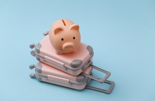 Travel, vacation or tourism concept. two mini travel luggage suitcase and piggy bank on a blue