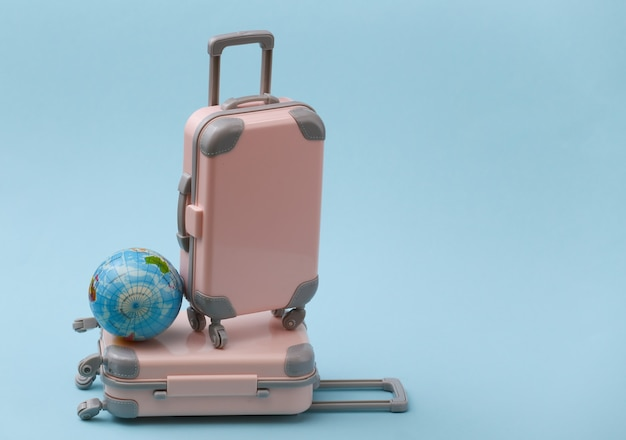Travel, vacation or tourism concept. two mini travel luggage suitcase with globe on a blue