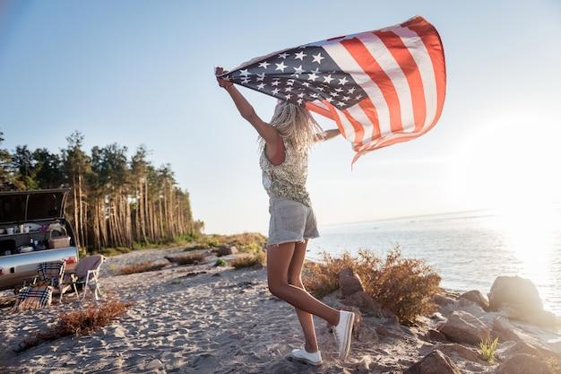Путешествуйте с флагом. американская патриотичная женщина в джинсовых шортах путешествует в компактном трейлере со своим флагом
