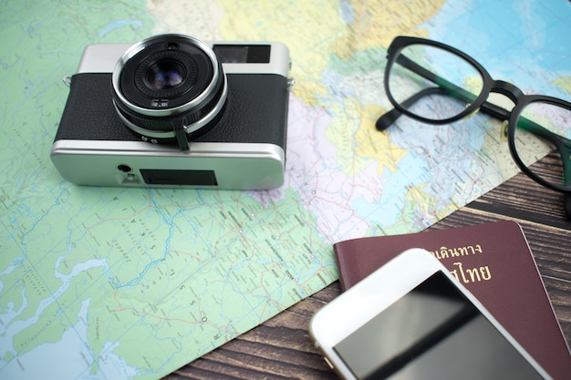 Travel with maps, film cameras, reading glasses and plasps on the old wooden surface.