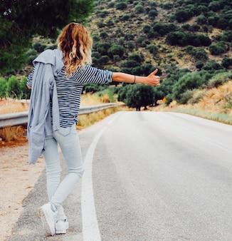 道路に沿ってヒッチハイクする女性を旅行します。休暇旅行中に道路で美しい女性。