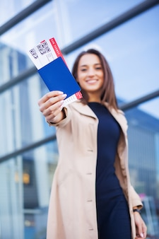 Travel, woman holding two air ticket in abroad passport near airport