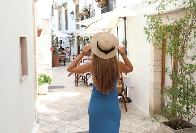 밀짚 모자와 이탈리아에서 휴가를 즐기는 파란 드레스 여행 여자