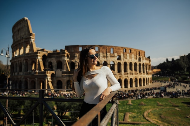 Travel woman standing and looking on coliseum, rome, italy.