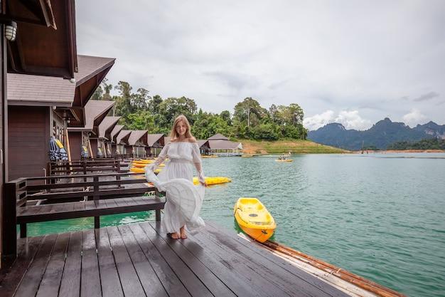 熱帯の山々のある湖の木造住宅の桟橋に立っている旅行女性