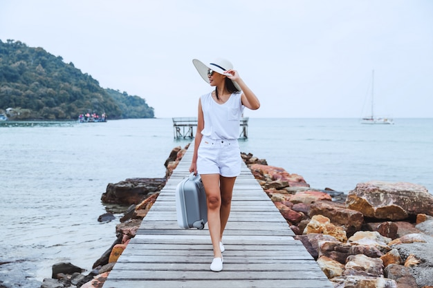 Travel woman with suitcase on beach