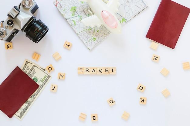 Viaggiare blocchi di legno; telecamera; carta geografica; banconote; passaporto e aereo su sfondo bianco