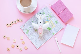 Travel wooden blocks; map; paper; tea cup; pen; diary and airplane on white surface